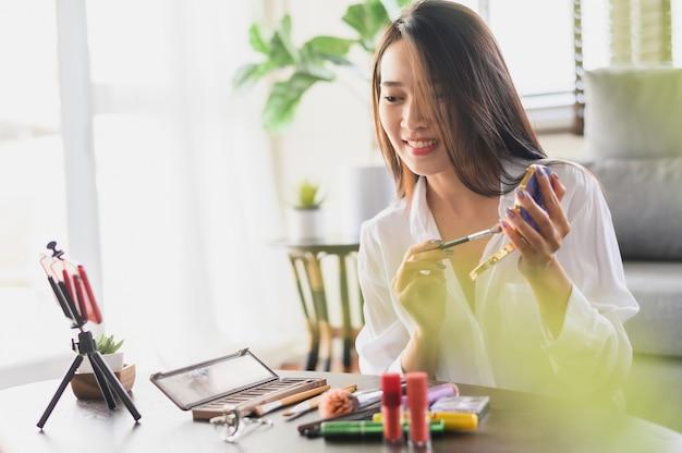 Азиатская женщина-блогер-красотка с помощью смартфона в прямом эфире рассматривает косметические продукты в гостиной дома