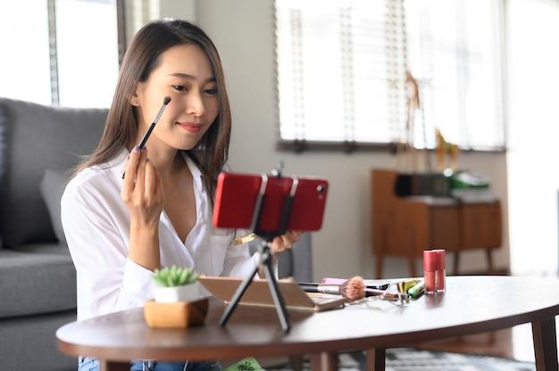 スマートフォンのライブストリーミングレビュー化粧品を使用している美容ブロガーインフルエンサーアジアの女性