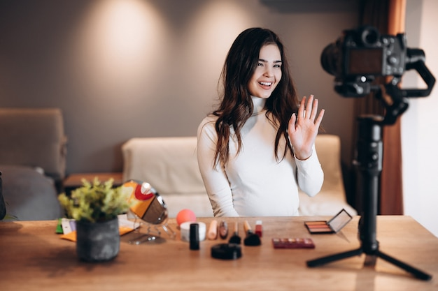 Beauty blogger nice female filming daily make-up routine tutorial on camera. influencer young woman live streaming cosmetics product review in home studio. vlogger job. diy putting makeup.