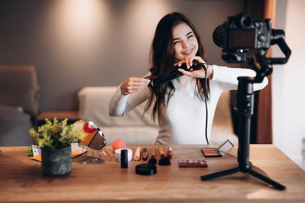 Бьюти-блогер милая женщина снимает ежедневный урок макияжа на камеру. влиятельная молодая женщина в прямом эфире транслирует обзор косметики в домашней студии. работа влогера. нанесение макияжа своими руками.