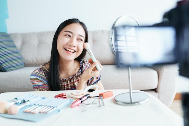 Бьюти-блогер азиатского женского туториала по макияжу косметики в прямом эфире транслирует потоковое видео.
