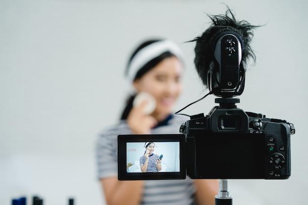 비디오를 녹화하기 위해 카메라 앞에 앉아있는 동안 뷰티 블로거 선물 뷰티 화장품