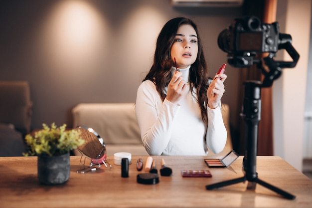 Beauty blogger pretty female filming daily make-up routine tutorial on camera. influencer young woman live streaming cosmetics product review in home studio. vlogger job. diy.