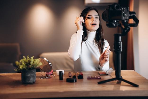 Бьюти-блогер симпатичная женщина снимает ежедневный урок макияжа на камеру. влиятельная молодая женщина в прямом эфире транслирует обзор косметики в домашней студии. работа влогера. сделай сам.