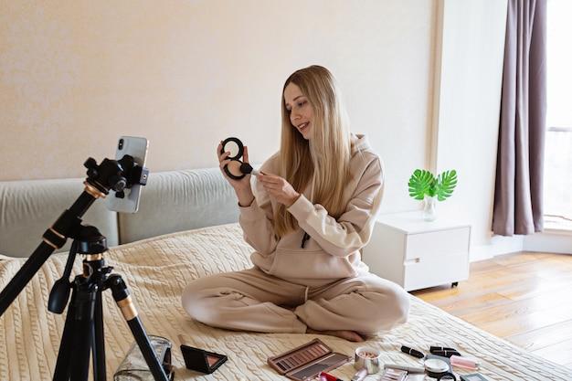 Beauty blogger recording makeup tutorial at home