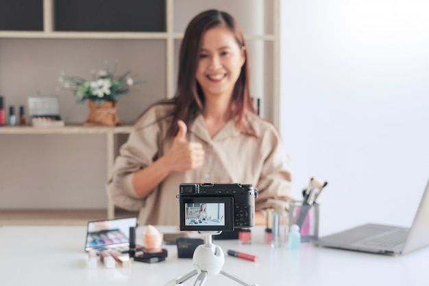 Beauty blogger recording video and presenting cosmetics at home