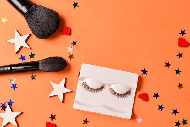 Текст блоггера красоты на оранжевом фоне. профессиональные модные продукты для макияжа с косметическими продуктами, тенями для век, ресницами, кистями и инструментами.