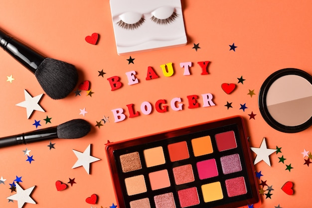 오렌지 배경에 뷰티 블로거 텍스트입니다. 화장품 미용 제품, 아이 섀도우, 속눈썹, 브러시 및 도구가 포함된 전문 유행 메이크업 제품.