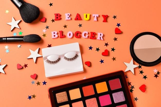 오렌지 벽에 뷰티 블로거 텍스트입니다. 미용 미용 제품, 아이섀도, 속눈썹, 브러쉬 및 도구가 포함 된 전문 트렌디 한 메이크업 제품입니다.
