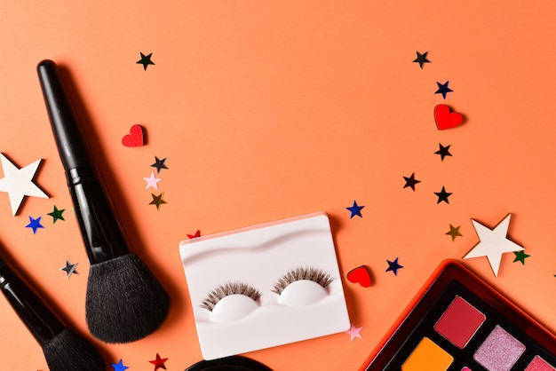 Beauty blogger text on an orange background. professional trendy makeup products with cosmetic beauty products,  eye shadows, eye lashes, brushes and tools.