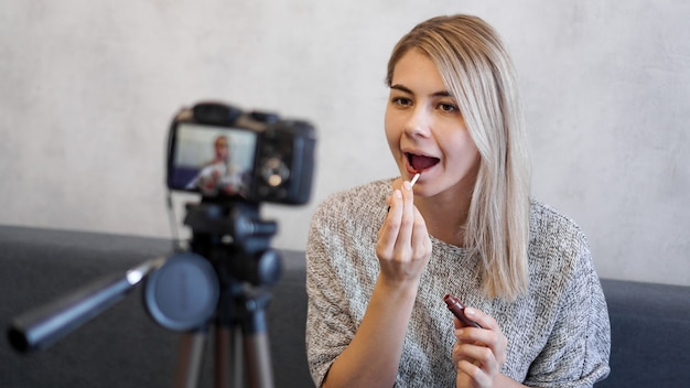 A beauty blogger or video blogger tells and shows subscribers how to do makeup. young woman paints lips