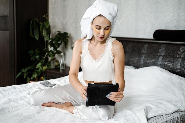 彼女の頭にパジャマタオルと化粧品で美容ブロガーvloggerインフルエンサー若い女性