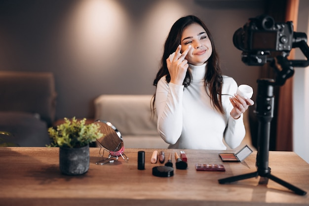 Beauty blogger woman filming daily make-up routine tutorial on camera. influencer young woman live streaming cosmetics product review in home studio. vlogger job. diy.