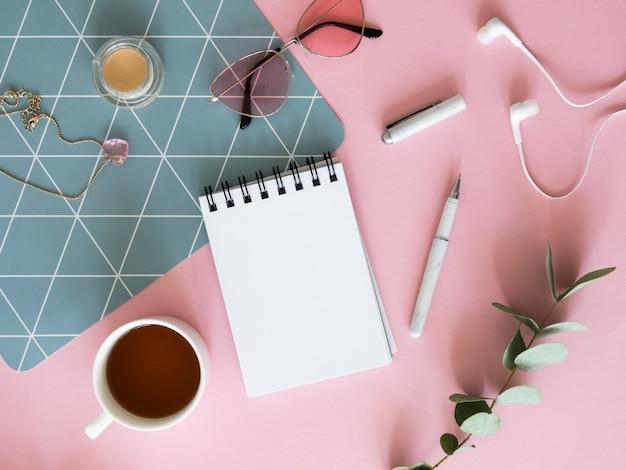 Макет рабочего пространства блоггера красоты. макет ноутбука, чай и косметические принадлежности на розовом столе. скопируйте место для вашего текста.