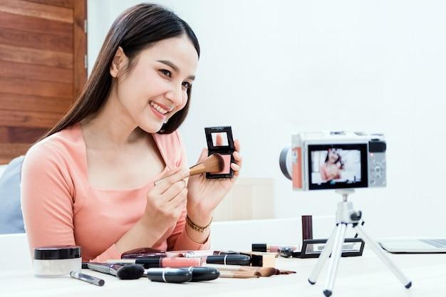 뷰티 블로거, 아름다운 아시아 여성들이 화장품을 이해하고 판매하기 위해 노력하고 있습니다. 온라인 스트리밍을 통해 카메라와 노트북을 사용하여 행복한 웃는 얼굴로 새로운 정상적인 비즈니스
