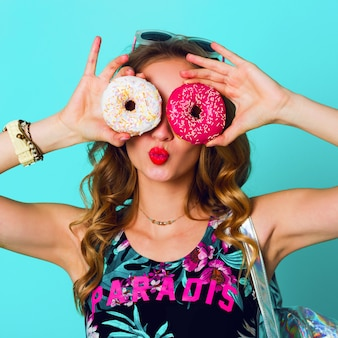 Beauty blonde  fashion model girl taking colorful pink  donuts. funny joyful woman with sweets, dessert. diet, dieting concept. junk food. bright colors.