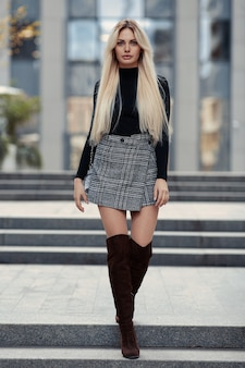 Beauty blonde girl walking in the street in style clothes