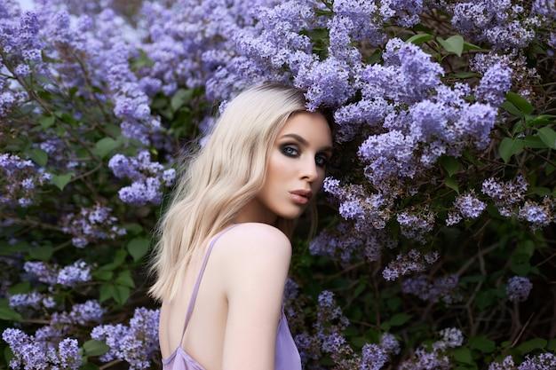 Красота белокурая женщина летом в кусте сирени. красота портрет девушки в фиолетовых цветах, красивый макияж