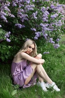 Beauty blonde woman in summer in a lilac bush. beauty portrait of a girl in purple flowers, beautiful makeup