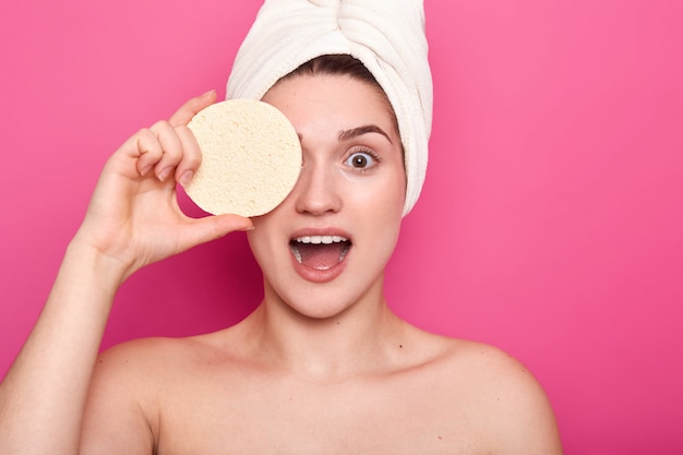 Beauty and body care concept. surprised young woman has smooth skin, cons eye with sponge, wears towel on head, shows bare shoulders, isolated on pink, going to remove makeup.