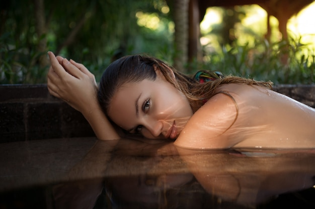 Beauty and body care. sensual young slim sexy girl relaxing in outdoor spa swimming pool. skin face care, hydrotherapy. woman enjoying summer holiday at resort hotel. spa, retreat, relaxation concept