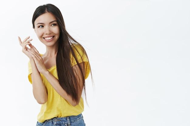 美しさ、ボディポジティブ、ナチュラルルックのコンセプト。黄色いtシャツを着た優しくてフェミニンなかわいい女性がポーズをとって広く笑っています