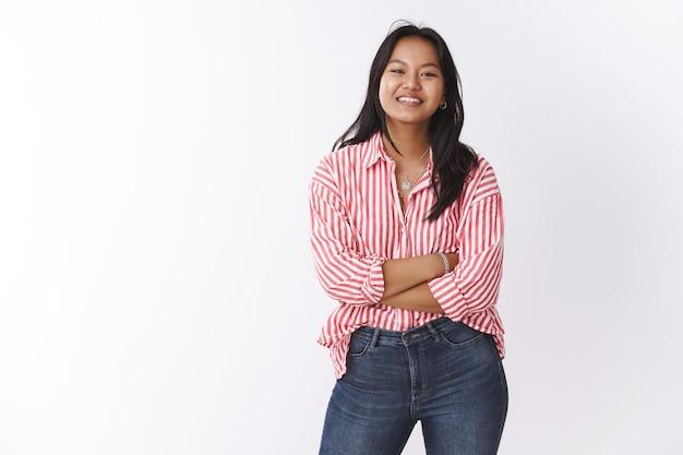Concetto di bellezza, corpo positivo ed emozioni. entusiasta simpatica donna vietnamita in camicetta da ufficio alla moda incrocia le mani sul petto sorridendo e ridendo parlando con gli amici sul muro bianco