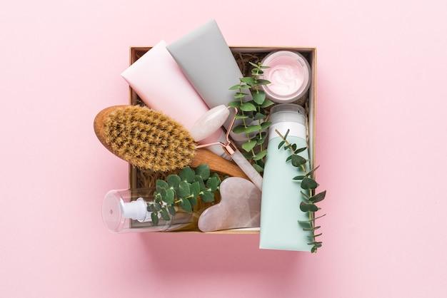ピンクの背景にフェイスケア製品とボディケア製品が入ったビューティーボックス
