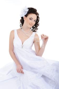 Sposa di bellezza in abito da sposa bianco con i capelli ricci