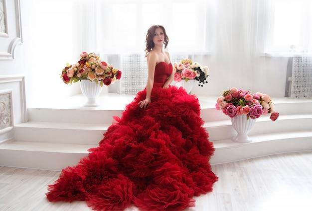 夜の赤いドレスの美しさブルネットモデルの女性。美しいファッションの豪華なメイクと髪型、フルレングス