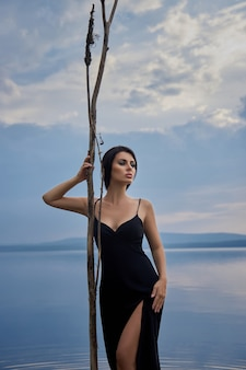 Beauty brunette woman in a black dress poses in a sea lake against a blue sky background. long hair sexy woman and beautiful beauty makeup on her face