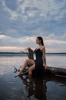 검은 드레스에 아름다움 갈색 머리 여자는 푸른 하늘 배경에 바다 호수에서 포즈. 긴 머리 섹시한 여자와 그녀의 얼굴에 아름다운 아름다움 메이크업