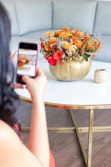 美しいブルネットの女性は、キャベツで描かれたカボチャの中のかわいい花の花束の写真を撮っています。