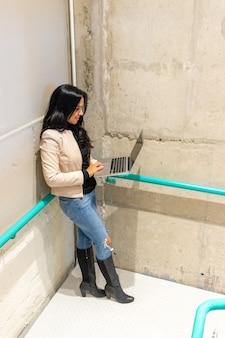 美しさのブルネットの女性は階段から彼女のラップトップで働いています