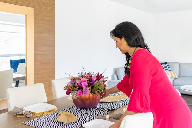 長い髪と赤いドレスの美しさのブルネットの女性は、別のハロウィーンを祝うために色の塗られたカボチャの中にフラワーアレンジメントでテーブルを飾っています