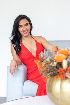 別のハロウィーンを祝うために色付きの塗装されたカボチャの中にフラワーアレンジメントと一緒に座っている長い髪と赤いドレスの美しいブルネットの女性