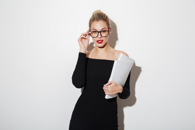 Beauty business woman in dress and eyeglasses holding documents