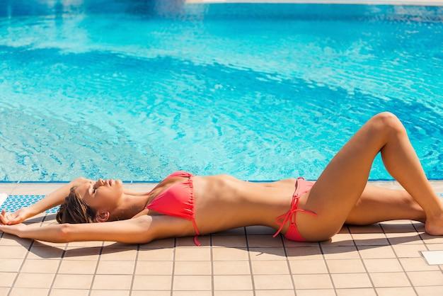 수영장 옆의 아름다움. 수영장 옆에 누워 눈을 감고 있는 비키니 입은 아름다운 젊은 여성