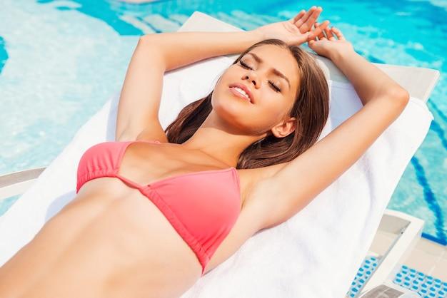 수영장 옆의 아름다움. 수영장 옆 갑판 의자에서 휴식을 취하는 비키니 입은 아름다운 젊은 여성의 최고 전망