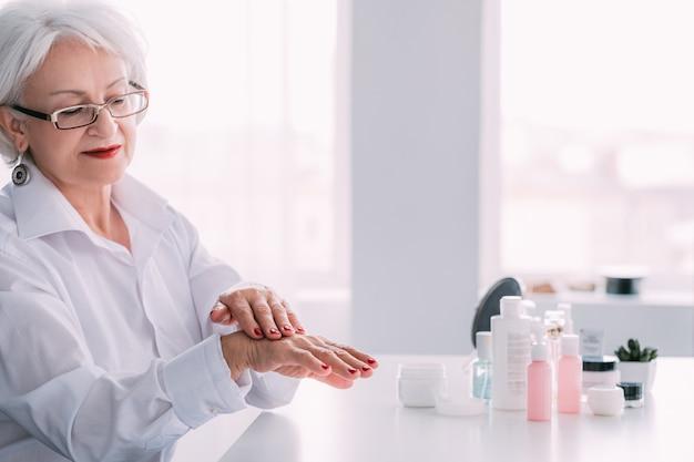 美容ケア。エイジハンドスキン製品。高価な化粧品を塗るおばあさん。
