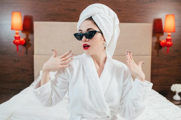 美容ケアとトリートメント。指を広げてベッドに座っているバスローブとターバンの若い女性。ホテルの部屋のインテリア。