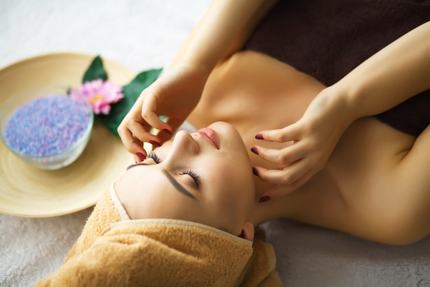 Beauty and care. cosmetologist makes face massage. young woman
