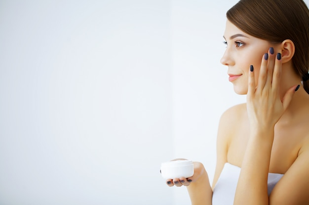 Beauty and care. happy smiling young woman holds cream for face. girl after shower. morning face care. pure skin. high resolution