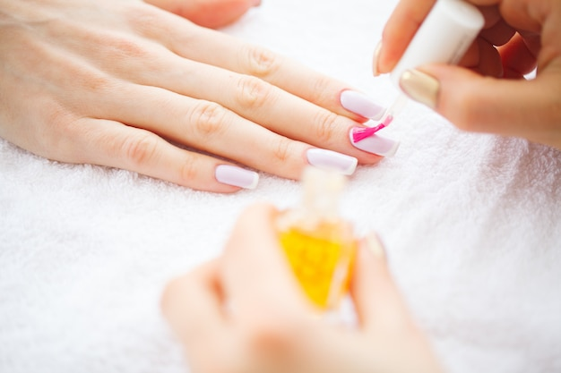 Beauty and care. manicure master applying nail polish in beauty salon. beautiful women's hands with perfect manicure. spa manicure