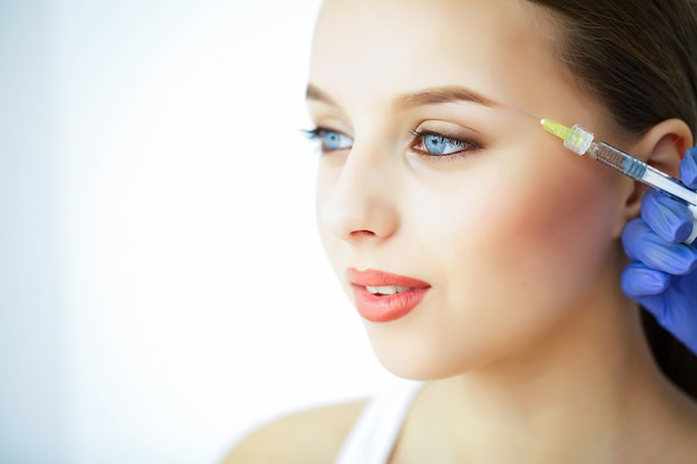 Beauty and care. portrait of a young woman with a beautiful face. a cosmetologist makes injections. high resolution