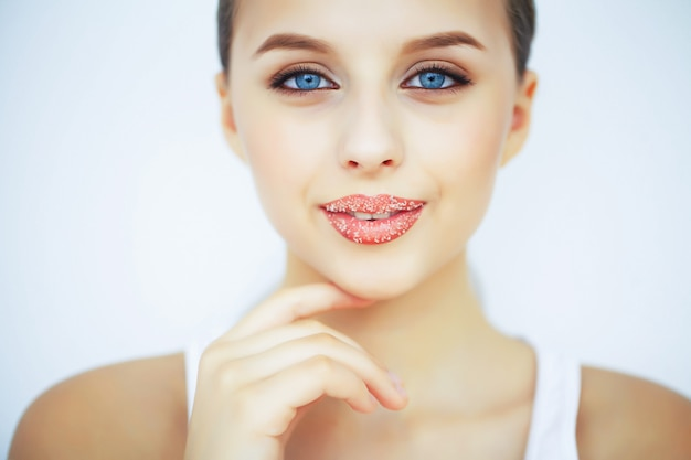 Beauty and care. portrait of a young woman with a beautiful skin. beautiful lips. girl takes care of lips. woman with beautiful blue eyes. makeup. lip scrub. peeling