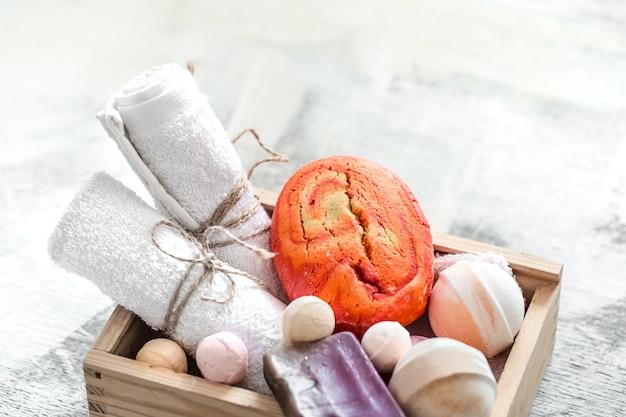 Косметические средства в деревянной коробке. мыло, полотенце с оранжевой бомбочкой для ванны. концепция спа или личной гигиены