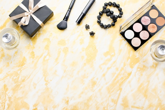Beauty care products, make up cosmetics on golden table top