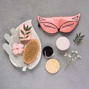 灰色のテクスチャ背景にスリーピングマスク、化粧用スポンジ、マッサージブラシグローブ型の手ぬぐいなどの美容製品。