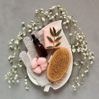 Beauty care set on the white plate among white flowers on gray background, skin treatment accessories.